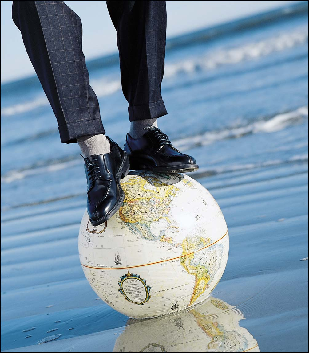 man standing on a globe wearing socks in the ocean