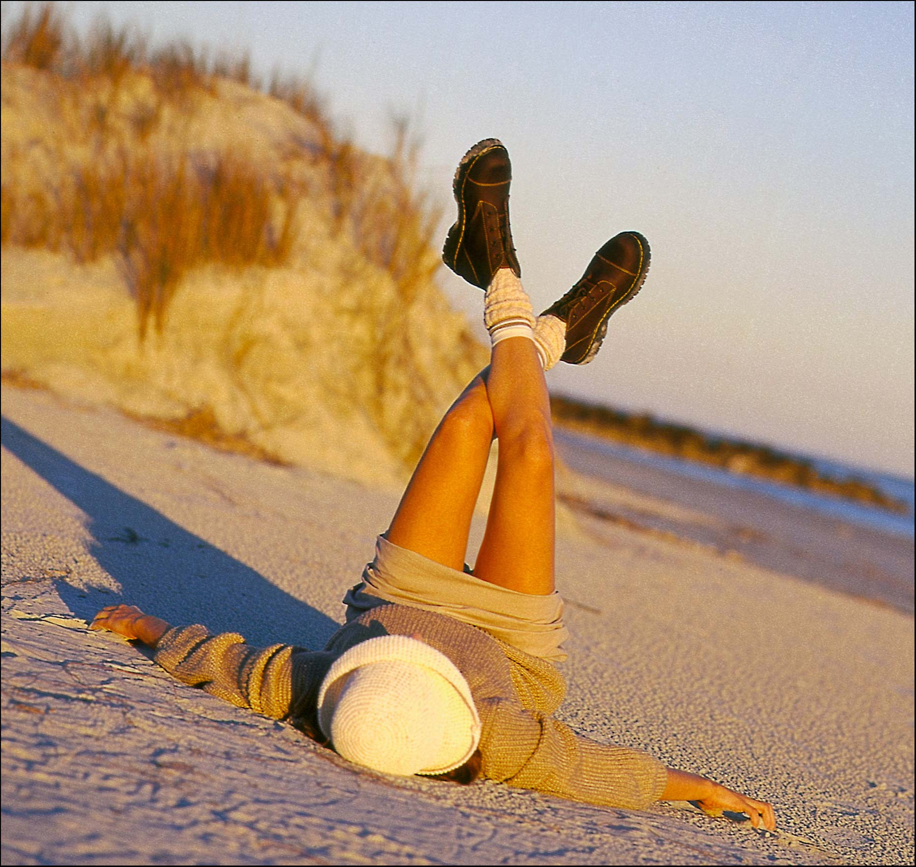 Girl lying on a beach wearing socks