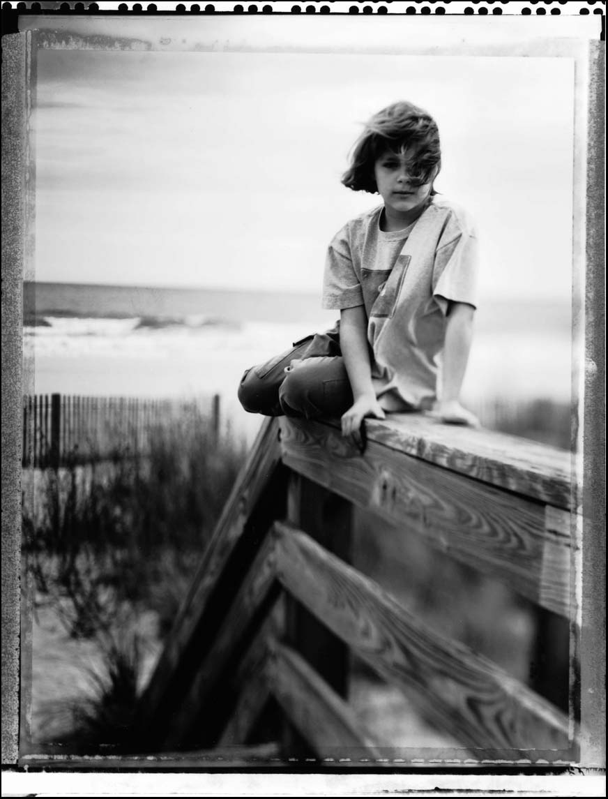 Black and white portrait of a Young girl on railing shot on Polaroid PN-55